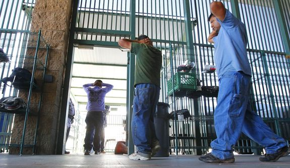 In this Thursday, Aug. 9, 2012, file photo, suspected illegal immigrants are transferred out of the holding area after being processed at the Tucson Sector of the U.S. Customs and Border Protection headquarters in Tucson, Ariz. (AP Photo/Ross D. Franklin, File)