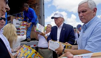 Republican presidential candidate Donald Trump and his running mate, Indiana Gov. Mike Pence, right, help to unload supplies for flood victims during a tour of the flood damaged area in Gonzales, La., Friday, Aug. 19, 2016. (AP Photo/Max Becherer)