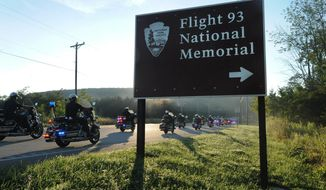 Motorcycles pass a sign near the  Flight 93 National Memorial near Shanksville, Pa., on Aug. 19, 2016. The America's 911 Ride begins at the Flight 93 crash site near Shanksville, and continues through Cumberland and Hagerstown, Md., before heading south through Leesburg, Va., to a hotel near the Pentagon. Organizer Ted Sjurseth says the 16th annual ride will be the last. (John Rucosky/The Tribune-Democrat via AP)