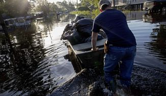 Daniel Stover, 17, moves a boat of personal belongings from a friend's home flooded home in Sorrento, La., Saturday, Aug. 20, 2016.  Louisiana continues to dig itself out from devastating floods, with search parties going door to door looking for survivors or bodies trapped by flooding. (AP Photo/Max Becherer)