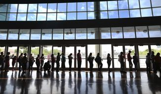 FILE - In this Monday, March 31, 2014 file photo, people line up to enroll for health insurance at the Alamodome in San Antonio, Texas, hours before the deadline in the first enrollment period of the Affordable Care Act. (Jerry Lara/The San Antonio Express-News via AP)