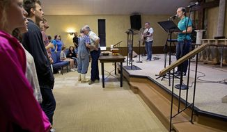 Pastor Mark Carroll, center right, hugs Robert Miller, center left, as the congregation sings during service at South Walker Baptist Church in Walker, La., Sunday, Aug. 21, 2016.  Outside the small town of Walker, Louisiana, the rural Baptist church has become an oasis for flood victims. (AP Photo/Max Becherer)