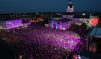 """People who could not get a ticket gather in Springer Market square to listen to the Tragically Hip in downtown Kingston, Ontario, Saturday, Aug. 20, 2016. The Tragically Hip mixed fan favorites, newer songs and some politics on Saturday night during the final show of their """"Man Machine Poem"""" tour. (Lars Hagberg/The Canadian Press via AP)"""