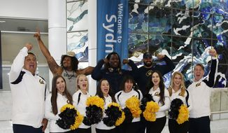 California Golden Bears cheerleaders welcome players as they arrive at Sydney International airport in Sydney, Australia, Monday, Aug. 22, 2016. A chartered Boeing 777 touched down at Sydney airport on Monday morning, delivering the California Golden Bears and team officials Down Under for their much-anticipated opening college football game of the season on Saturday against Hawaii. (AP Photo/Rob Griffith)