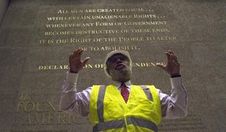 In this photo taken July 18, 2016, Museum Director Lonnie Bunch stands in-front of one of the engraved walls of the Smithsonian's National Museum of African American History and Culture in Washington, during a media preview tour. The museum's grand opening will be on Sept. 24. (AP Photo/Paul Holston)