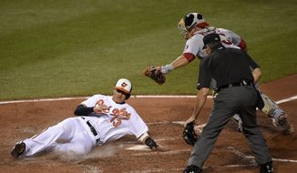 Baltimore Orioles' Manny Machado (13) slides home to score past Washington Nationals catcher Wilson Ramos, right, and home plate umpire Angel Hernandez, center, on a double by Chris Davis during the fourth inning of a baseball game, Monday, Aug. 22, 2016, in Baltimore. (AP Photo/Nick Wass)