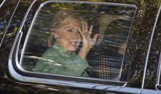 Hillary Clinton waves from her motorcade vehicle as she arrives for a fundraiser at the home of Justin Timberlake and Jessica Biel in Los Angeles on Tuesday. (Associated Press)