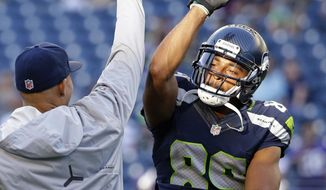 FILE - In this Aug. 18, 2016, file photo, Seattle Seahawks wide receiver Doug Baldwin, right, high-fives tight end Jimmy Graham before the team's preseason NFL football game against the Minnesota Vikings, in Seattle. Last season was a career year for Baldwin. He tied for the NFL lead in TD receptions and was rewarded by the Seahawks with a contract extension in the offseason.(AP Photo/Elaine Thompson, File)