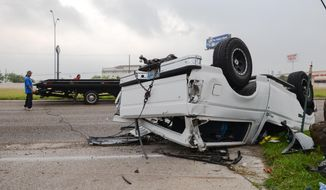In this April 28, 2016, file photo, a wrecker crew prepares to flip over a Ford Bronco that was involved in an accident in Brownsville, Texas. (Jason Hoekema/The Brownsville Herald via AP, File)