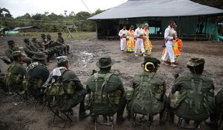 In this Aug. 16, 2016 photo, rebels of the the 32nd Front of the Revolutionary Armed Forces of Colombia perform folk dances in front of their comrades at their camp in the southern jungles of Putumayo, Colombia. The FARCs southern bloc, to which the front belongs, is one of the rebel army's oldest and most belligerent fighting units. (AP Photo/Fernando Vergara)