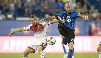 Montreal Impact defender Laurent Ciman, right, and D.C. United midfielder Rob Vincent vie for the ball during the first half of an MLS soccer match Wednesday, Aug. 24, 2016, in Montreal. (Paul Chiasson/The Canadian Press via AP)