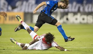 Montreal Impact midfielder Marco Donadel, top, battles with D.C. United forward Kennedy Igboananike during the first half of an MLS soccer match Wednesday, Aug. 24, 2016, in Montreal. (Paul Chiasson/The Canadian Press via AP)