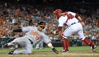 Baltimore Orioles' Manny Machado (13) slides home past Washington Nationals catcher Wilson Ramos to score on single by Jonathan Schoop during the eighth inning of a baseball game, Wednesday, Aug. 24, 2016, in Washington. The Orioles won 10-8. (AP Photo/Nick Wass)