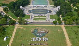 This photo provided by the National Park Service shows people on the National Mall in Washington, looking toward the World War II Memorial, Thursday, Aug. 25, 2016, creating a giant, living version of the National Park Service emblem. Participants used brown, green and white umbrellas to create the emblem. (Tim Ervin/National Park Service via AP)