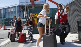 In this Wednesday, Aug. 24, 2016, photo, a Port Authority customer care representative helps arriving passenger Katie Smith, of Chicago, find a temporary taxi pickup location outside of Terminal B at LaGuardia Airport in New York, where a $4 billion upgrade is underway. To alleviate traffic congestion, no taxis are being allowed to pick up arriving passengers at the lower level of the terminal, where demolition and construction have caused more than the ordinary traffic congestion. (AP Photo/Kathy Willens)