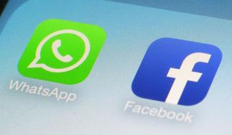 This Feb. 19, 2014, file photo, shows WhatsApp and Facebook app icons on a smartphone in New York. (AP Photo/Patrick Sison, File)