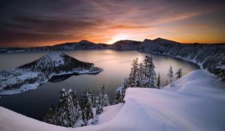 ,FILE - In this January 2006, file photo, the sun rises over Crater Lake, Ore., in Crater Lake National Park. Crater Lake lies in the caldera of an ancient volcano called Mount Mazama that collapsed 7,700 years ago, according the the National Parks Service. It is the deepest lake in the United States and is famous for its vivid blue color and water clarity. (Marc Adamus/The Register-Guard via AP, File)