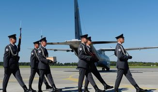 A wooden urn with the ashes of Polish fighter ace Capt. Kazimierz Sporny, credited with downing at of least five enemy planes in the Battle of Britain,is carried  with military honors at the Krzesiny Air Base in Poznan, Poland on Thursday, August 25, 2016, after being brought from London for a military burial in his hometown. The burial ceremony of Sporny, who died in Britain in 1949 was part of ceremonies honoring Poland's Air Force at a time when the conservative government attaches great importance to defense because of Russia's actions in western Ukraine. (AP Photo)