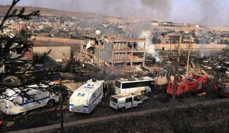 Smoke still rises from the scene after Kurdish militants attacked a police checkpoint in Cizre, southeast Turkey, Friday, Aug. 26, 2016, with an explosives-laden truck, killing several police officers and wounding dozens more, according to reports from the state-run Anadolu news agency. (DHA via AP)