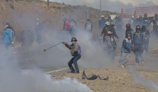Independent miners clash with the police as they run from clouds of tear gas during  protests in Panduro, Bolivia, Thursday, Aug. 25, 2016. Thousands of independent miners continued their protests with roadblocks which precipitated the clashes as the police attempted to dislodge them. (AP Photo/Juan Karita)