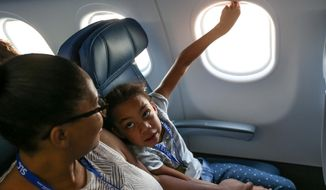Bianca Mittendorf, of Ogden, and her daughter, Maya Whiten, 7, take a simulated flight at Salt Lake International Airport on Saturday, Aug. 20, 2016. Taking Flight for Autism is a program that allows children with autism and their families and get acquainted with the routines and sounds of air travel by staging a mock flight. (Spenser Heaps/Deseret News via AP)