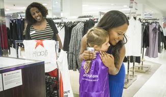 The March of Dimes' purple-caped crusader Sidney Hornfeck, center encourages customer Nadia Lewis, right, to participate in Macy's 11th annual Shop For A Cause by giving $5 at the register to receive a shopping savings pass on Saturday, Aug. 27, 2016, in Atlanta. All proceeds benefited the March of Dimes in their quest for mom and baby health. (John Amis/AP Images for Macy's) ** FILE **