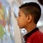Syrian refugee Hamzeh Jouriyeh, 12, studies a map of the United States in the Amman, Jordan, office of the International Organization for Migration. (Associated Press)