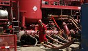 A worker steps through the maze of hoses being used at a remote fracking site in Rulison, Colo. (Associated Press)