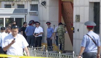 Kyrgyz police officers examine broken gates to the Chinese Embassy in Bishkek, Kyrgyzstan, Tuesday, Aug. 30, 2016. A suspected suicide bomber on Tuesday crashed a car through the entrance of the Chinese Embassy in the Kyrgyzstan capital of Bishkek, detonating a bomb that killed the attacker and wounded three embassy employees. (AP Photo)