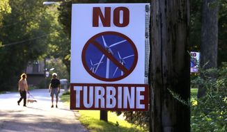 In this Thursday, Aug. 25, 2016 photo, a sign against a proposed wind turbine hangs from a neighborhood telephone pole, in North Smithfield, R.I. Even as Rhode Island makes history as the first U.S. state with an offshore wind farm, its people are not so fond of wind turbines sprouting up on land near where they live. Town leaders in North Smithfield are proposing a ban on any new wind turbines in the rural community near the Massachusetts border. (AP Photo/Charles Krupa)