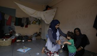 A woman plays with a child at an abandoned hospital wing, which is used as a makeshift shelter for about 150 Syrian refugees in Athens, Wednesday, Aug. 31, 2016. Over 59,000 people remain stranded in the country, most in army-built camps on the mainland and about 7,800 refugees are receiving hotel vouchers or live in vacant apartments. (AP Photo/Thanassis Stavrakis)