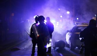 In this Nov. 25, 2014, file photo, police officers watch protesters as smoke fills the streets in Ferguson, Mo. (AP Photo/Charlie Riedel, File)