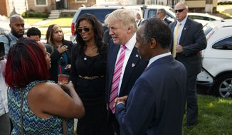 Neighborhood resident Felicia Reese, left, talks with Republican presidential candidate Donald Trump and Dr. Ben Carson, during a tour of Carson's childhood home, Saturday, Sept. 3, 2016, in Detroit. (AP Photo/Evan Vucci)