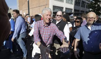 Former President Bill Clinton shakes hands as he marches with union members in the annual Labor Day parade, Monday, Sept. 5, 2016 in Detroit. (AP Photo/Carlos Osorio)