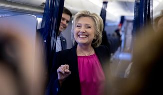 Democratic presidential candidate Hillary Clinton, accompanied by Traveling Press Secretary Nick Merrill, left, smiles as she speaks to members of the media as her campaign plane prepares to take off at Westchester County Airport in Westchester, N.Y., Tuesday, Sept. 6, 2016, to head to Tampa for a rally in Tampa. (AP Photo/Andrew Harnik)