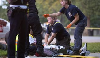 Members of the Chicago Fire Department work on a gunshot victim at the scene of a double shooting in Ogden Park Monday, Sept. 5, 2016, in the Englewood neighborhood of Chicago. Thirteen people were shot to death over the Labor Day weekend in Chicago, making it the deadliest holiday weekend of one of the deadliest summers the city has experienced in decades.  (Erin Hooley/Chicago Tribune via AP)