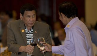Philippine's President Rodrigo Duterte toasts a drink with Brunei Foreign Minister and Prime Minister Sultan Hassanal Bolkiah during Association of Southeast Asian Nations (ASEAN) summit welcome dinner in Vientiane, Laos, Tuesday, Sept. 6, 2016. (AP Photo/Gemunu Amarasinghe)