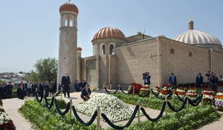 Uzbekistan's Prime Minister Shavkat Mirziyayev, center, places flowers, as Russian President Vladimir Putin stands at left of him, during a minute of silence at a cemetery in Samarkand, Uzbekistan, Tuesday, Sept. 6, 2016. Putin arrived to express his condolences and visit a grave of Uzbekistan's President Islam Karimov in Samarkand. (Alexei Druzhinin/Sputnik, Kremlin Pool Photo via AP)