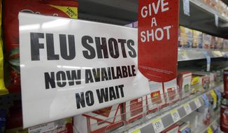 A sign telling customers that they can get a flu shot in a Walgreens store is seen in Indianapolis on Sept. 16, 2014. (Associated Press) **FILE**