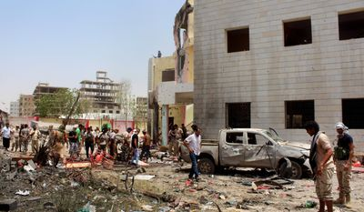 Fighters loyal to the government gather at the site of a suicide car bombing in Aden, Yemen, on Monday. The bombing claimed by the Islamic State group in Aden killed over 50 pro-government troops who had been preparing to fight Houthi rebels. (ASSOCIATED PRESS)