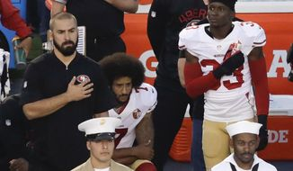 FILE - In this Thursday, Sept. 1, 2016 file photo, San Francisco 49ers quarterback Colin Kaepernick, middle, kneels during the national anthem before the team's NFL preseason football game against the San Diego Chargers, in San Diego. NFL Commissioner Roger Goodell disagrees with Kaepernick's choice to kneel during the national anthem, but recognizes the quarterback's right to protest.  (AP Photo/Chris Carlson, File)