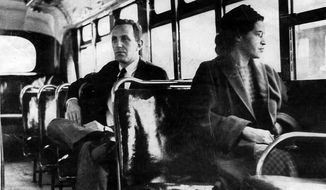 This an undated photo shows Rosa Parks riding on the Montgomery Area Transit System bus. Parks refused to give up her seat on a Montgomery bus on Dec. 1, 1955, and ignited the boycott that led to a federal court ruling against segregation in public transportation. (Associated Press)