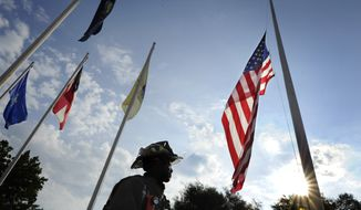 As the early morning sun begins to break above the trees, firefighter Alwyn Chandler, with the Fort Gordon Fire Department, stands beneath the flag following a 9/11 remembrance ceremony at Fort Gordon, Ga., Friday,  Sept. 9, 2016.   (Michael Holahan/The Augusta Chronicle via AP)