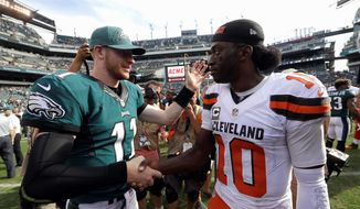 Quarterback Robert Griffin III (right) struggled in his Cleveland Browns debut in a 29-10 loss on Sunday to rookie quarterback Carson Wentz and the Philadelphia Eagles. (Associated Press)