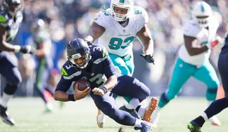 Miami Dolphins defensive tackle Ndamukong Suh (93) steps on Seattle Seahawks quarterback Russell Wilson's foot in the third quarter of an NFL football game in Seattle, Sunday, Sept. 11, 2016. (Dean Rutz/The Seattle Times via AP)