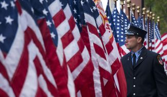 An FDNY firefighter walks among flags at the FDNY Memorial Wall near the World Trade Center Sunday, Sept. 11, 2016, on the 15th anniversary of the attacks on the World Trade Center in New York. (AP Photo/Craig Ruttle)