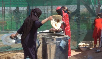 An Iraqi woman bakes bread in makeshift ovens at a U.N. refugee camp in Fallujah, Iraq. Thousands of Iraqi civilians flooded camps around Fallujah after U.S.-backed Iraqi forces ousted Islamic State from the city in late June. (Carlo MuNoz/The Washington Times)