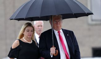 FILE - In this Aug. 24, 2016 file photo, Republican presidential candidate Donald Trump walks in the rain with Florida Attorney General Pam Bondi as they arrive at a campaign rally in Tampa, Fla. Facing the toughest stretch of her campaign, Hillary Clinton is trying to deflect attention back onto her rival Donald Trump, with a new push to highlight complaints surrounding his now-defunct Trump University, and allegations of pay-to-play involving Florida Attorney General Pam Bondi.(AP Photo/Gerald Herbert, File)