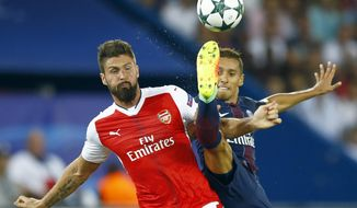PSG's Marquinhos, right, challenges for the ball with Arsenal's Olivier Giroud during the Champions League group A soccer match group between Paris Saint Germain and Arsenal at the Parc des Princes stadium in Paris, Tuesday, Sept. 13, 2016. (AP Photo/Francois Mori)