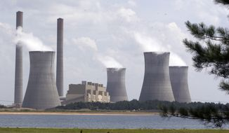 In this July 10, 2007, file photo, the coal-fired Plant Scherer is in operation at Juliette, Ga. Most Americans are willing to pay a little more each month to fight global warming, but only a tiny bit, according to a new poll. (AP Photo/Gene Blythe, File)